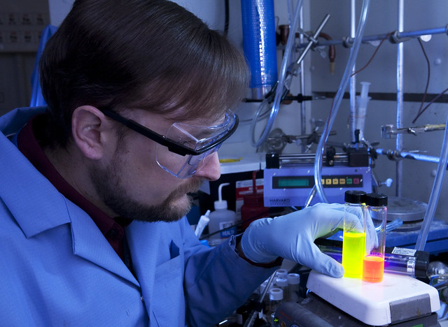 Researcher Jeff Pietryga shows two vials of different-size nanocrystals, each emitting light of a different color (energy) that corresponds to the nanocrystal's size (and energy gap).  Photo by LeRoy Sanchez.