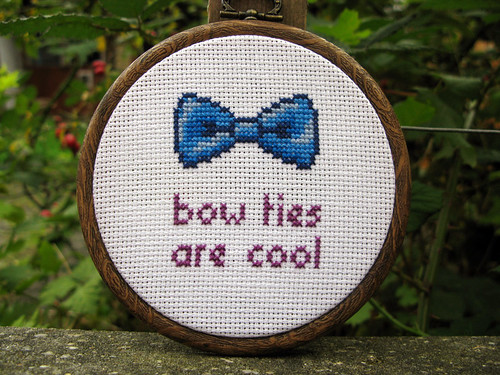 A cross-stitched pattern of a blue bow tie, below it in red letters it says BOW TIES ARE COOL