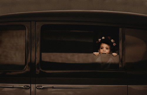 Flowergirl playing in vintage car.