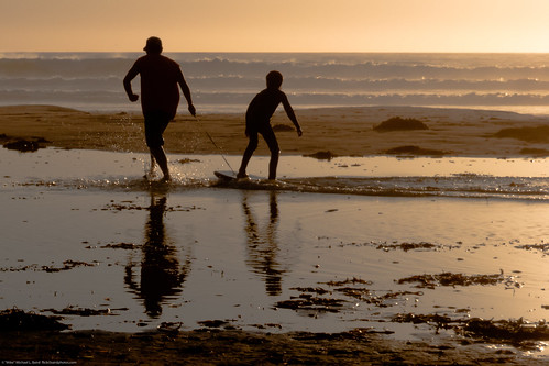 Father and son playing and bonding on Bogey-Board on Morro Strand State Beach