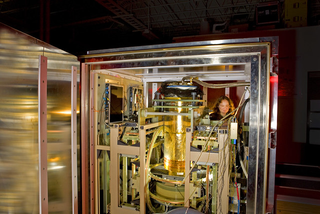 A member of the SQUID team at Los Alamos National Laboratory (LANL), with the apparatus used to study MRI at ultralow magnetic fields. The copper coils that produce the magnetic fields are wound on wooden armatures to avoid the magnetic distortions caused by metal.  Photo by LeRoy Sanchez.