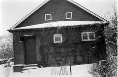 barn(0.0), history(0.0), chapel(0.0), building(1.0), winter(1.0), farmhouse(1.0), snow(1.0), shack(1.0), cottage(1.0), house(1.0), monochrome photography(1.0), sugar house(1.0), monochrome(1.0), home(1.0), black-and-white(1.0),