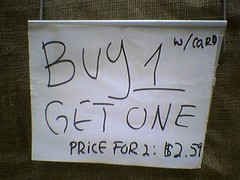 "Supermarket ""sale"" sign: ""BUY 1 GET ONE, W/CARD. PRICE FOR 2: $2.59"""