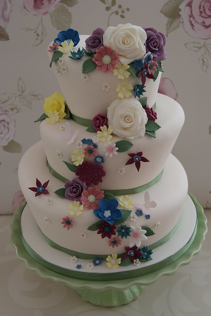 A wonky three tiered wedding cake with a colourful cascade of summer flowers