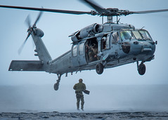 A Sailor jumps from an MH-60 Sea Hawk helicopter off the coast of Guam.