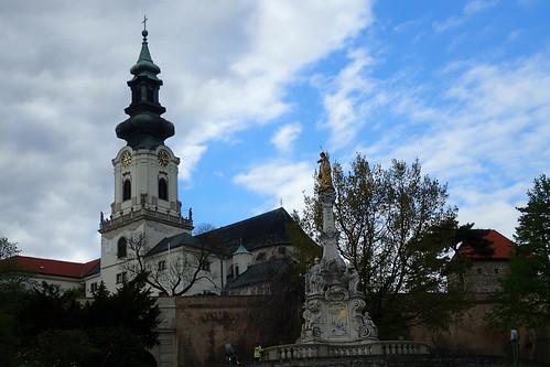 statue fontaine clocher église nuages arbres mur passants nitra château slovaquie historique vieilleville horloge