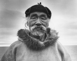 An elderly Inuit man, Aarulaq, wearing a duffle parka and smoking a pipe, Shugliaq, Nunavut / Un aîné inuit, Aarulaq, vêtu d'un duffle parka et fumant une pipe, à Shugliaq (Nunavut)