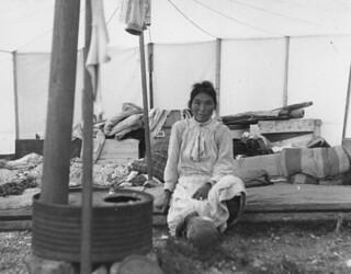 Inuit woman sitting inside a tent that has a stove, Kangiqsujuaq, Quebec / Inuite assise dans une tente munie d'un poêle, Kangiqsujuaq (Québec)e008446973-v6