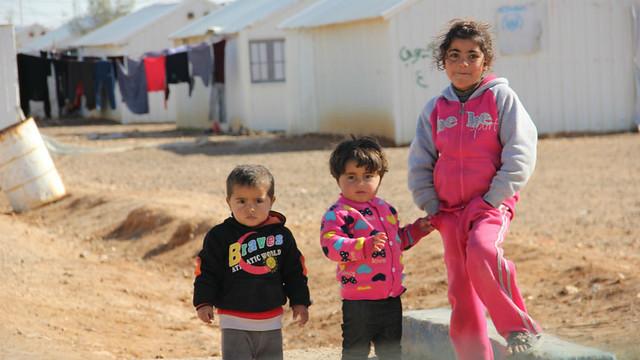 Three refugee children standing in a camp