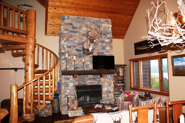 Floor to ceiling stone fireplace, hand crafted log circular stairway, superb lake and mountain views