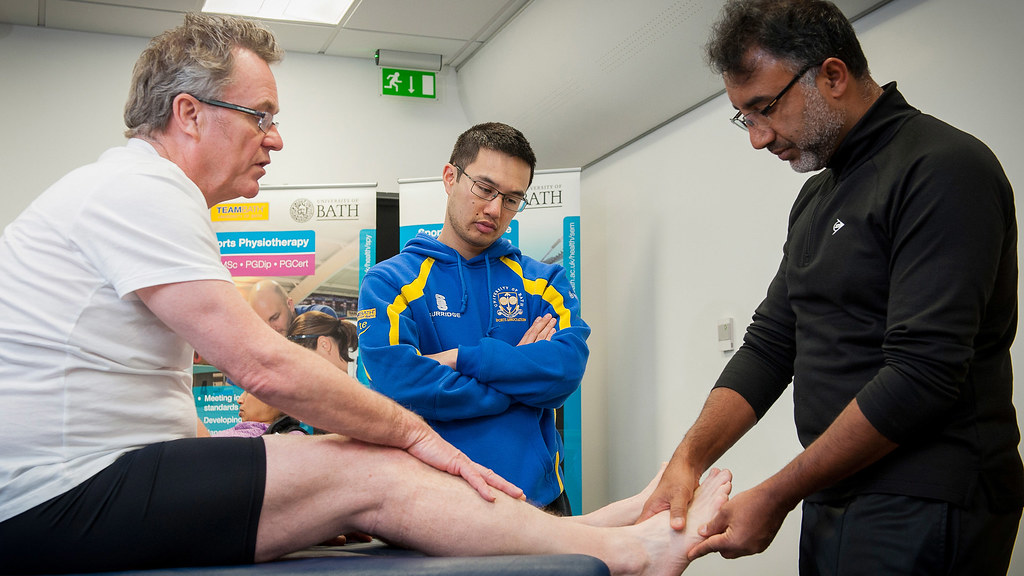 Medical staff check out a sports injury watched by a student