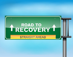 """Highway sign with """"Road to recovery """" text"""