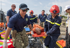 Hospital Corpsman 2nd Class Gustavo Llerenas, left, and other Pacific Partnership team members work with Vietnamese emergency responders during a search and rescue and oil spill response field training exercise, May 13. (U.S. Navy/MC2 Joshua Fulton)