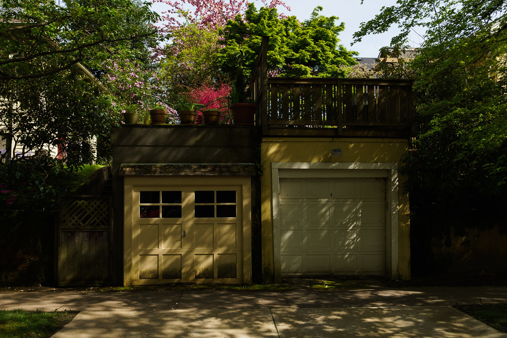 Sun dappled yellow garages on a spring morning