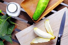 Banana and cucumber on a wooden cutting mat