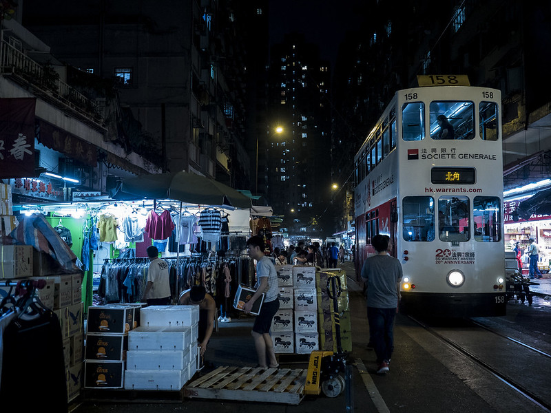 Tram running through night market