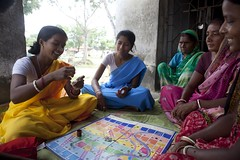 Hensla Village, Arsa Block, Purulia District, West Bengal, India. 30 September 2011: 23 year old, Ila Pal ( Left, yellow sari) demonstrates the method of using condoms to village women and members of the Red Ribbon Club ( RRC) during a game of Snakes and