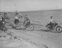Four men riding motorcycles, Carleton, Quebec / Quatre hommes en motocyclette, Carleton (Québec)