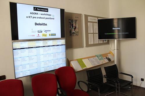 LCD obrazovky s logy partnerů, rozvrhem a prezentačním videem společnosti Deloitte, hlavního partnera Agory pro letošní rok