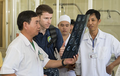 Lt. Cmdr. Justin Dye of Navy Medical Center San Diego examines neurological injury patients with local doctors at Khahn Hoa General Hospital, May 22. (U.S. Navy/MC2 Joshua Fulton)