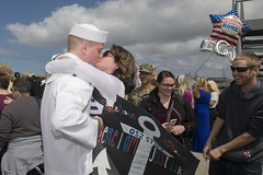Operations Specialist 2nd Class Zackary Stiff kisses his wife upon his return from deployment aboard the amphibious assault ship USS Makin Island, May 15. (U.S. Navy/MCSN Morgan K. Nall/)
