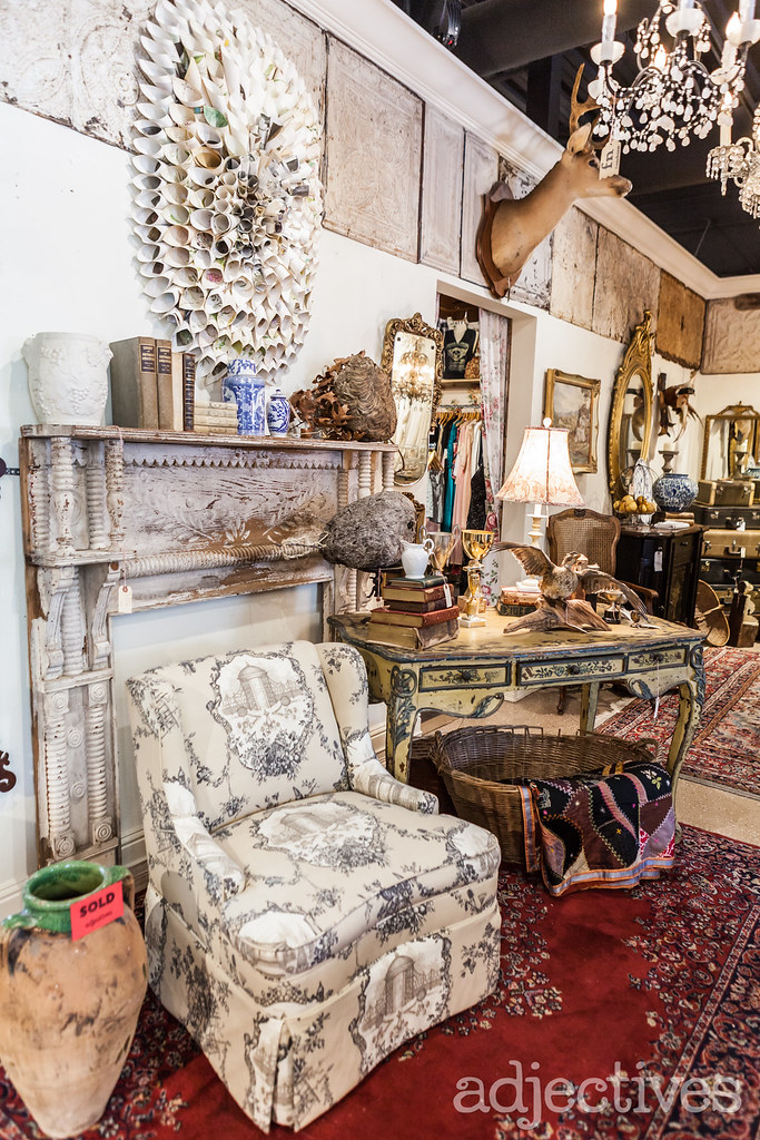 Antique desk, upholstered chair and rustic mantel at Adjectives Winter Park by The French Nest