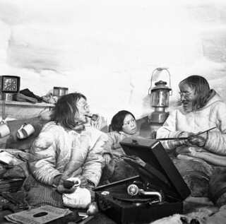 Niviaqsarjuk makes caribou footwear and Kangirjuaq works on a snow knife while their grandson Ikkat listens to music... / Niviaqsarjuk fabrique des chaussures en peaux de caribou et Kangirjuaq entretient son couteau à neige pendant que leur petit-fil