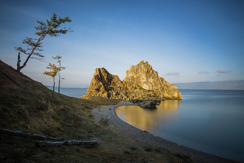 olkhon lake baikal rock shamanka khuzir russia sibiria refelctions sunlight yellow fall autumn water russian island beach clouds long exposure