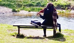 Musician by a river