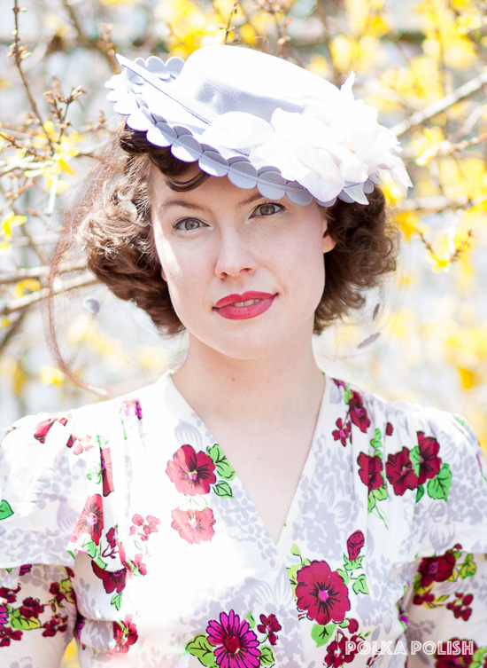 1940s pale periwinkle tilt hat with circle decoration around the edge and white millinery flowers paired with a 1940s rayon dress in magenta, burgundy, and lime
