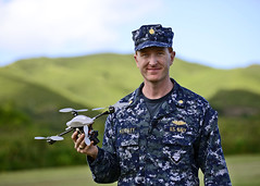 Lt. Cmdr. Christopher Keithley poses for a photo holding an unmanned aerial vehicle. (U.S. Navy/MC1 Phillip Pavlovich)