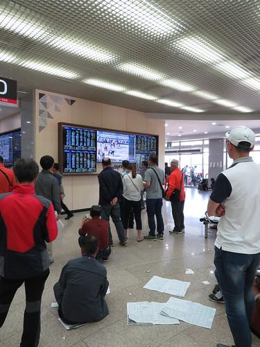 釜山慶南競馬場場外モニター前でレースを眺める人々