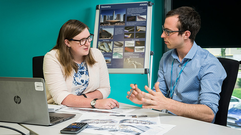 Student and colleague sit at a table in an office discussing technical plans in front of them
