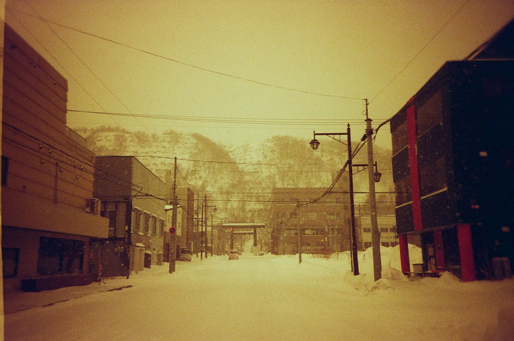 稚内 Wakkanai, Japan / Redscale / Lomo LC-A+ 抵達後的隔天早上,準備前往最北的宗谷岬,走回車站的一路上變成白天的景色,原來昨晚大雪背後是襯托這樣的街景。  遠遠看過去是一個神社外的鳥居,還滿喜歡這樣靜靜的街道。  但一天下來,都是這樣安靜,似乎沒有店家開門營業。  你曾經為某人敞開心胸了,但她卻沒有走進來過。  Lomo LC-A+ Lomography Redscale XR 50-200 35mm 0399-0017 2017-01-23 ISO100 Photo by Toomore