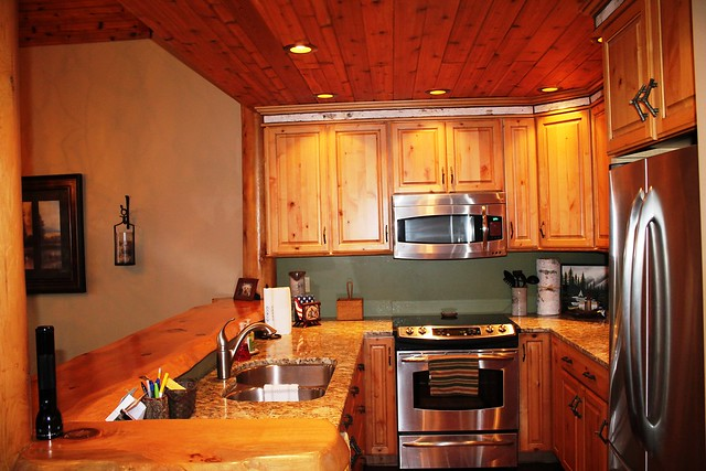 Massive log slab counter tops, custom cabinets, stainless steel appliances;