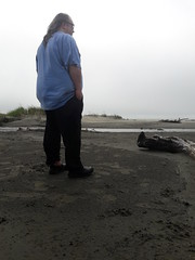 Reflecting on the beach, blue t-shirt, black pants, shoes, sun glasses, driftwood, gray sand, grasses, overcast day, Ocean Shores, Washington, USA
