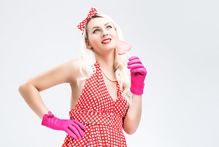 Pinup Retro Concepts. Dreaming Sensual Pinup Blond Woman With Sweet Candy Posing in Polka Dotted Dress on White.