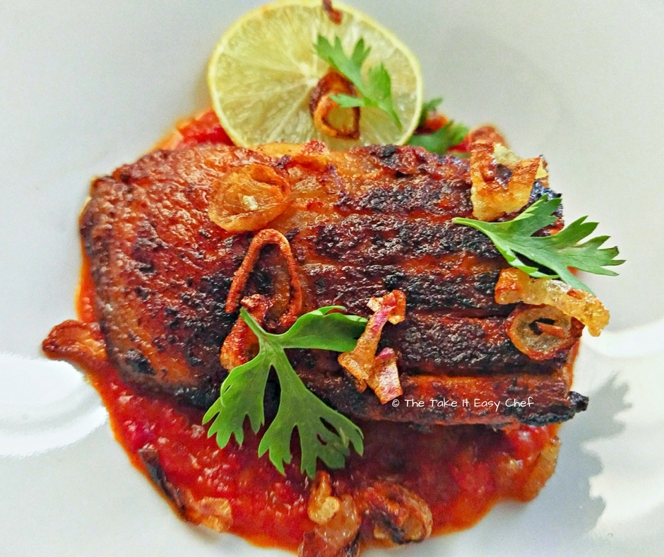 Pan-fried masala sea bass served on layer of tomato-chilli paste, and garnished with fried shallots and coriander leaves