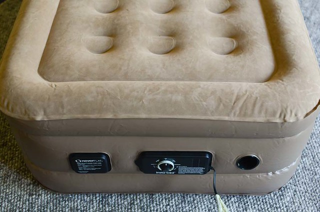 brown air mattress on gray rug with controls
