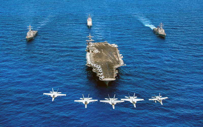 F/A-18 Hornets and Super Hornets fly over USS Carl Vinson and ships.