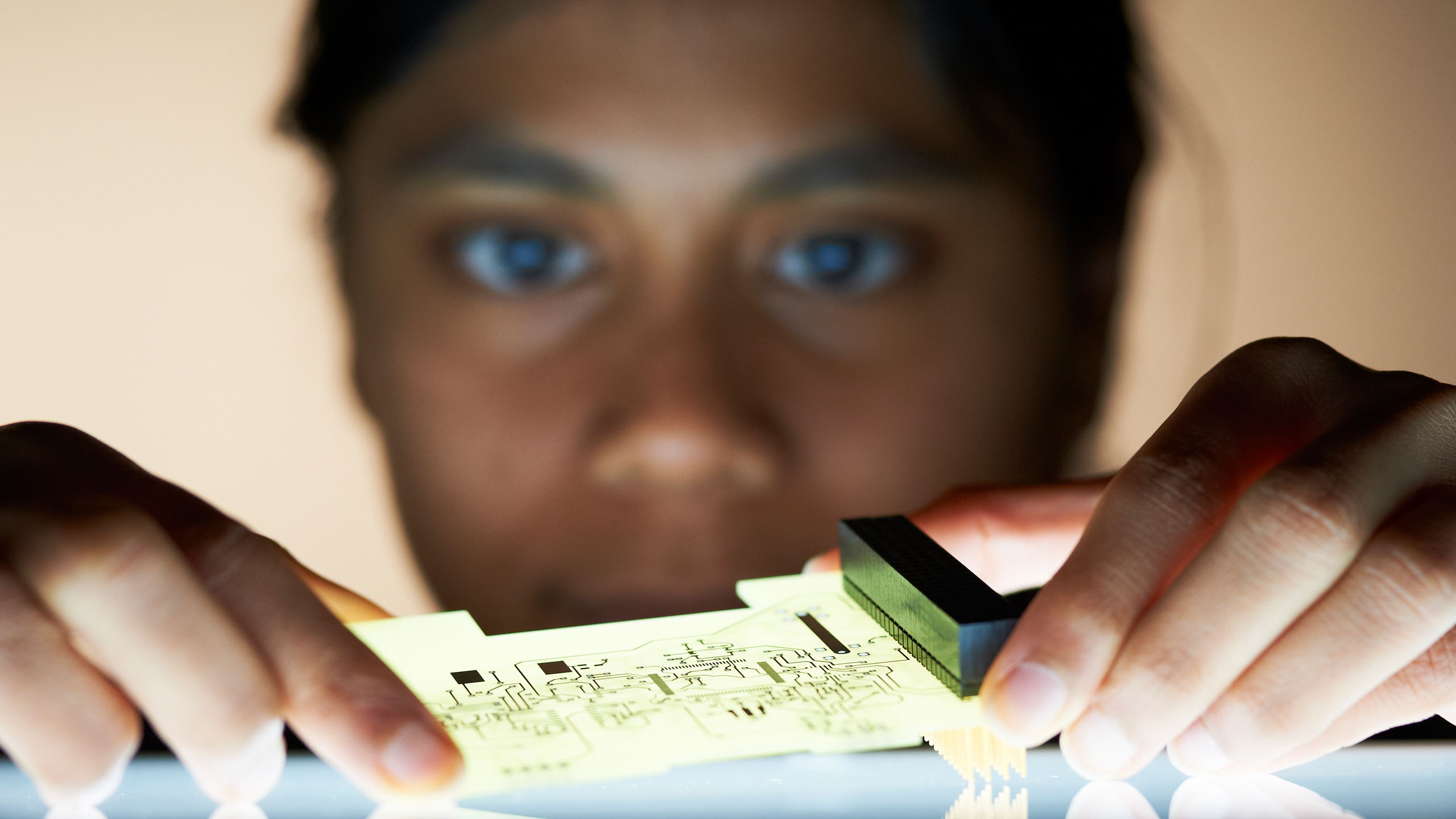 A close up of a student holding a circuit board