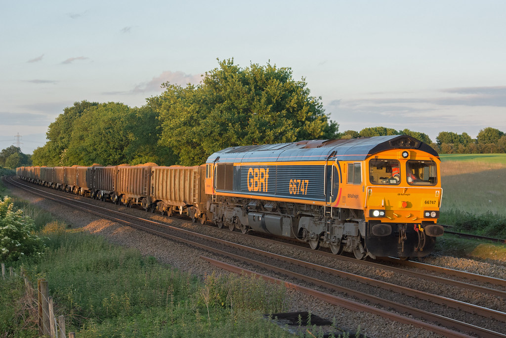 66747 Hethersett 30/05/17 - Former European 'Shed' 66747 catches the final glimpses of evening sun at Hethersett on the 30/05/17. 6M56 has just started the journey towards Wellingborough from Trowse, hauling a consist of loaded sand JNA wagons.