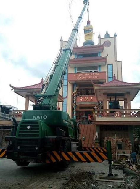 Proses penurunan rupaka Buddha Vihara Tri Ratna Tanjung Balai, Sumatera Utara dengan menggunakan crane. Foto: Facebook