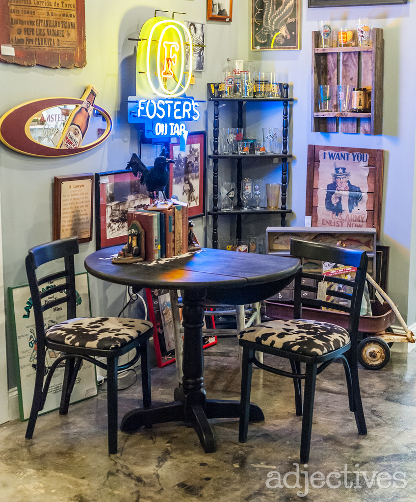 Black painted dining set with cowhide chairs and vintage Foster's Beer Light sign by Gone Fishing at Adjectives Altamonte
