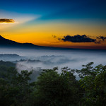14. Juuni 2017 - 6:07 - The Borobudur Temple is in the centre covered by mist. The sun just came up from the back of Mt. Merapi and Mt. Merbabu. The picture was taken from Punthuk Setembu about 5 km away from the temple.