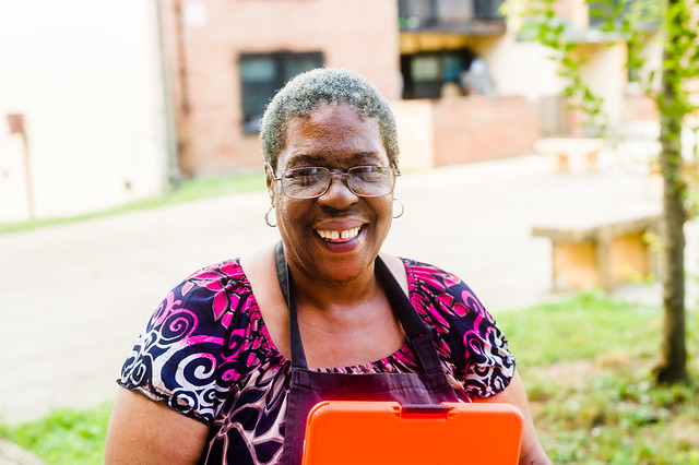 Charlean Griffin, a Benning Terrace resident, holds an orange clipboard with the Urgent Wellness survey on it.