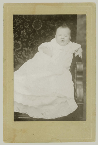 Card mounted portrait of baby in smock