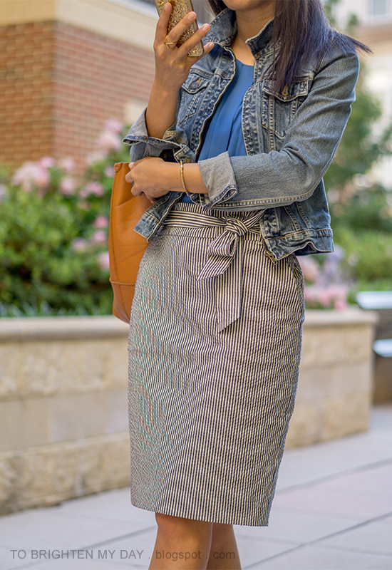 denim jacket, bright blue pleated top, gold jewelry, striped paperbag pencil skirt with bow