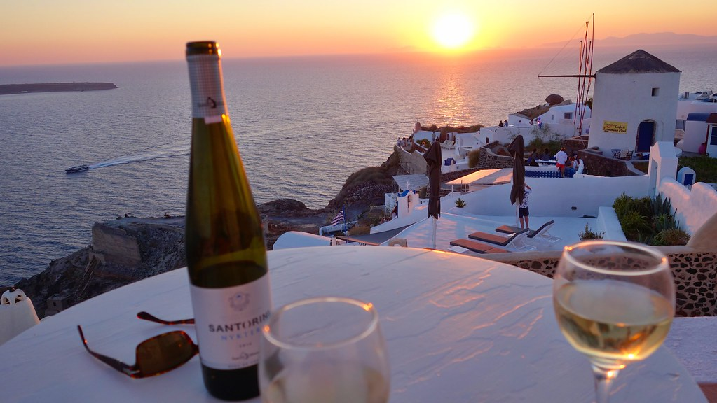 Santorini sunset with a glass of Santorini wine