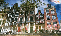 The reflection of typical narrow houses with large windows in the canal, Amsterdam